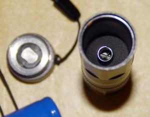 Кнопка включения-выключения снята; показан аккумуляторный отсек, подпружиненный контакт, никакой маркировки с указанием полярности нет